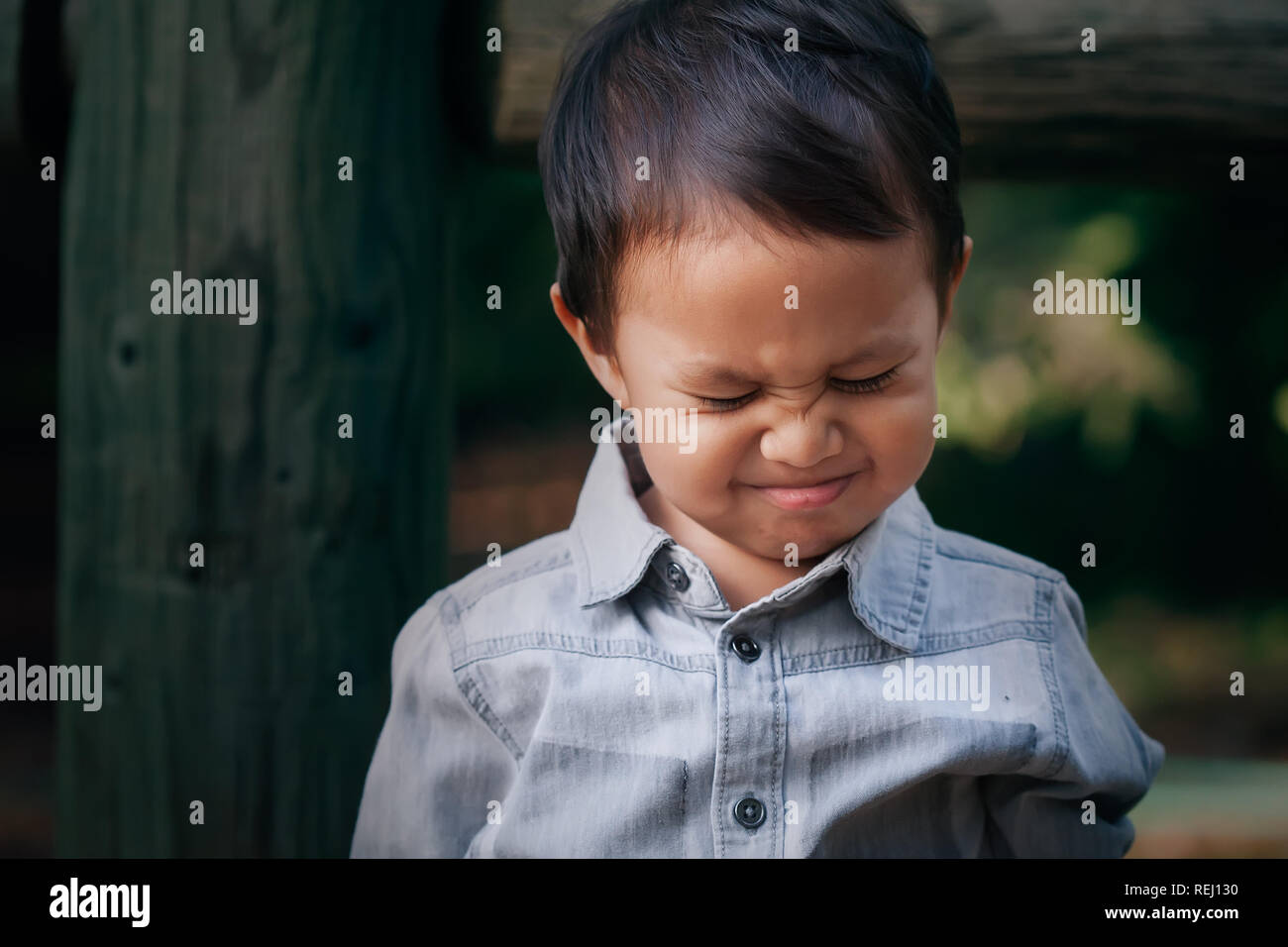 A little boy crying or throwing a temper tantrum with a frowned face, associated with emotional distress. - Stock Image