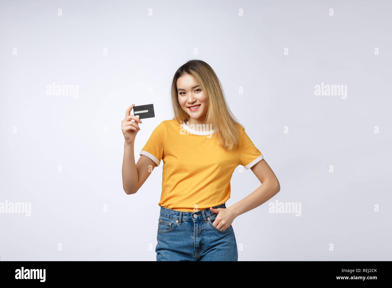 Asian content woman holding fan of money dollar banknotes and credit card and looking on copyspace isolated over gray background. - Stock Image