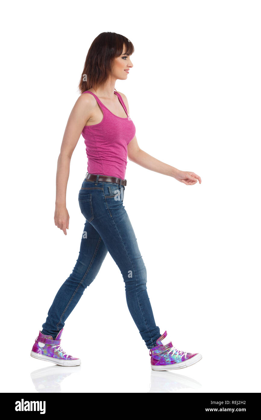 Young woman in jeans, magenta tank top and sneakers is walking and looking away. Side view. Full length studio shot isolated on white. - Stock Image