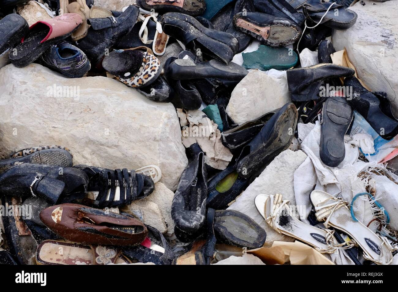 A pile old shoes dumped on the rocks on the coast - Stock Image