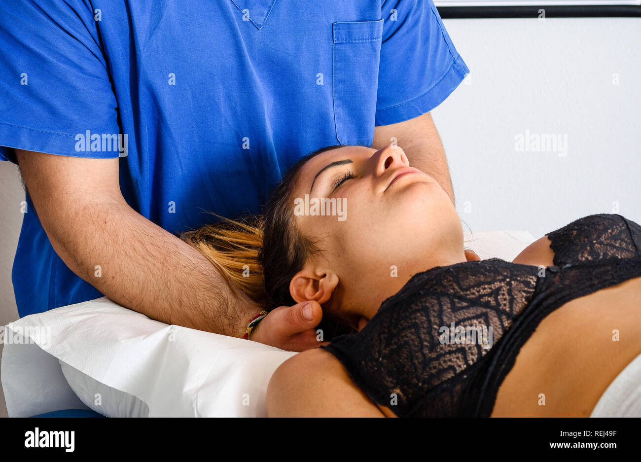 Osteopath manipulating the neck of a young woman as she lies on a couch in his consulting room in a close up view on his hands - Stock Image