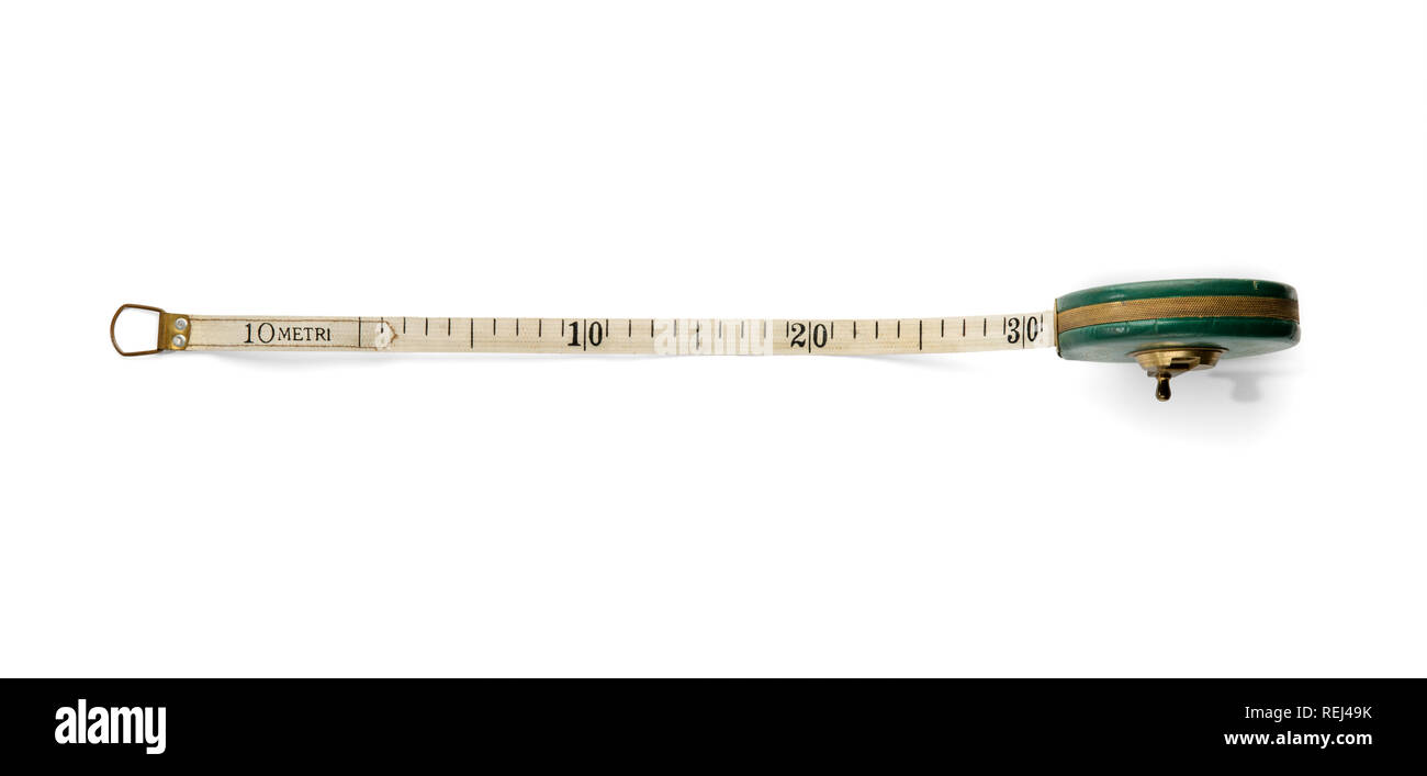 Retractable ribbon measuring tape marked in centimeters with a winding roll-up mechanism viewed partially extended over white from above - Stock Image
