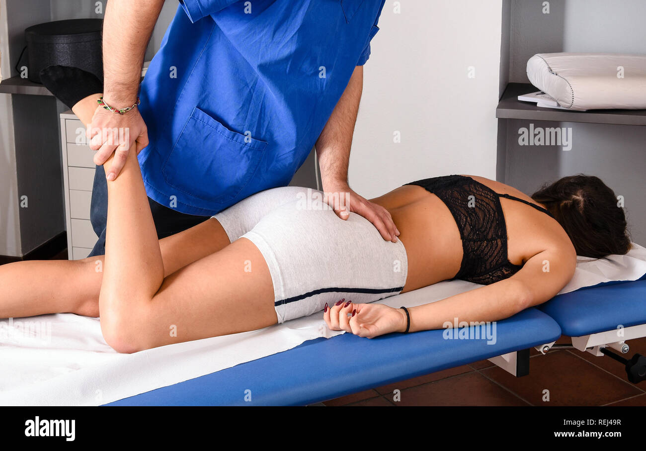 Male osteopath treating the knee of a female patient using his hands to realign and readjust the bones of the joint as she lies on a couch in his cons - Stock Image