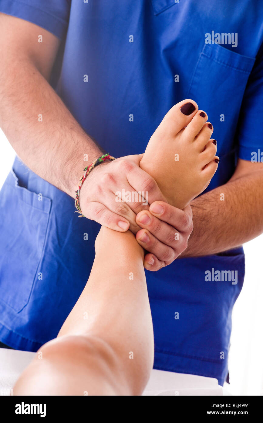 Male osteopath massaging the foot of a woman applying pressure with his hands to readjust and manipulate her foot in an alternative medicine concept - Stock Image