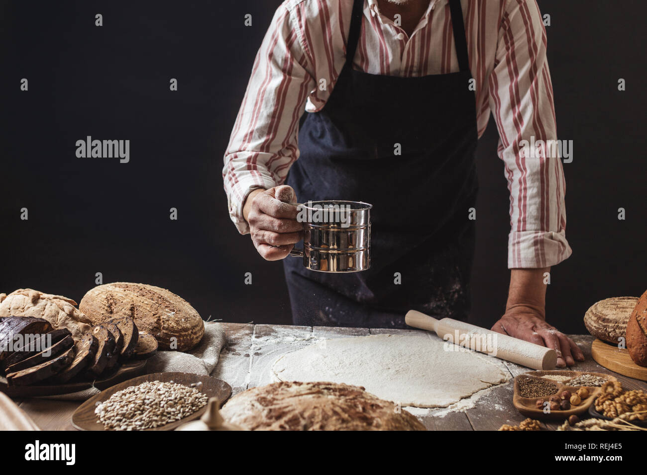 Man sprinkling some flour on dough. Hands kneading dough, cropped view - Stock Image