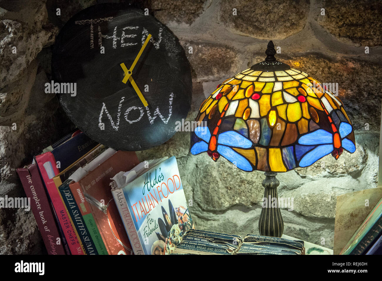 domestic kitchen scene, cook books,Tiffany Reproduction Stained Glass Lamp Shade table lamp, slate face clock, Then and now written in chalk - Stock Image