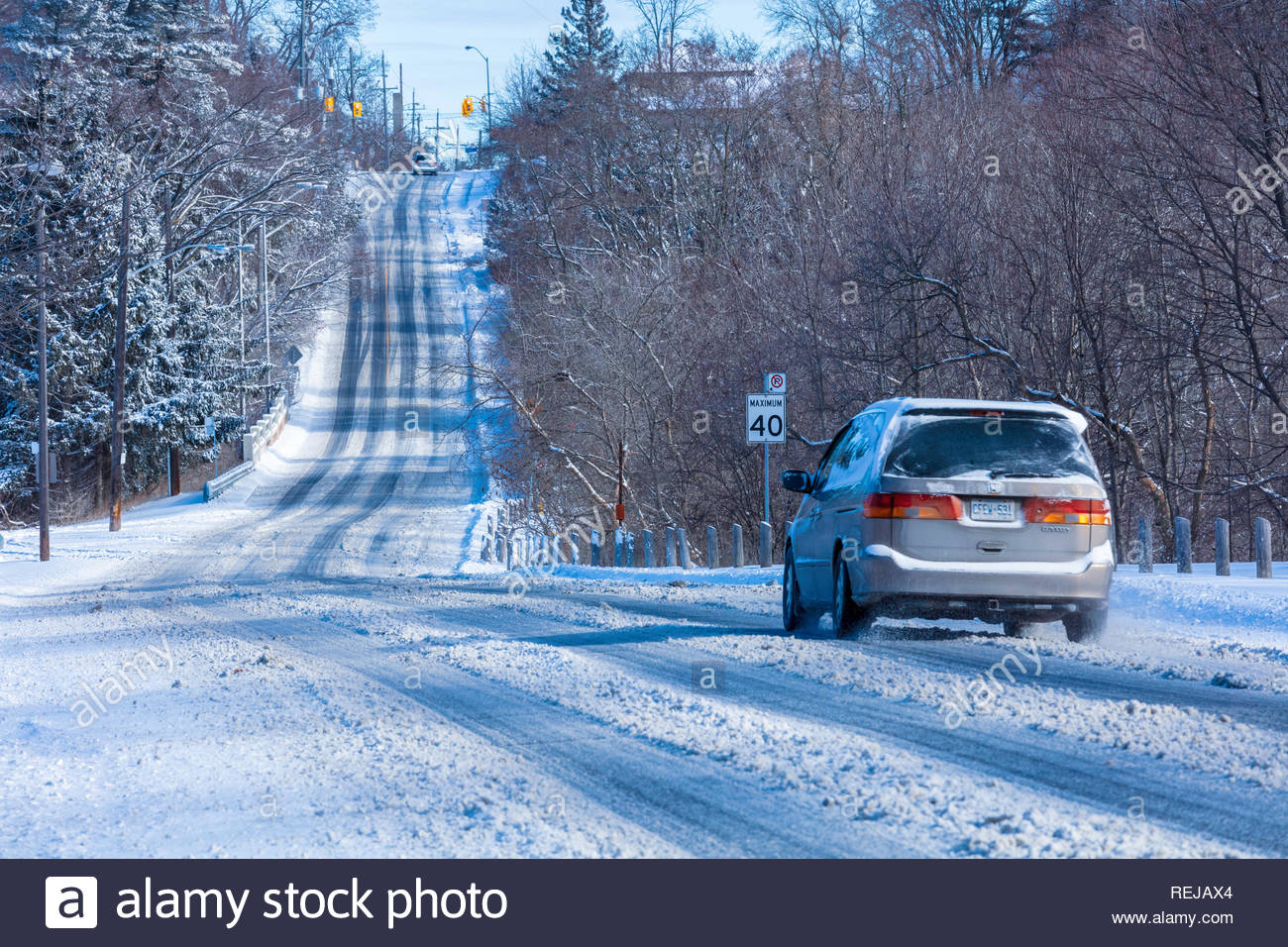 Bad winter driving conditions on a snow covered road in Toronto Ontario Canada - Stock Image