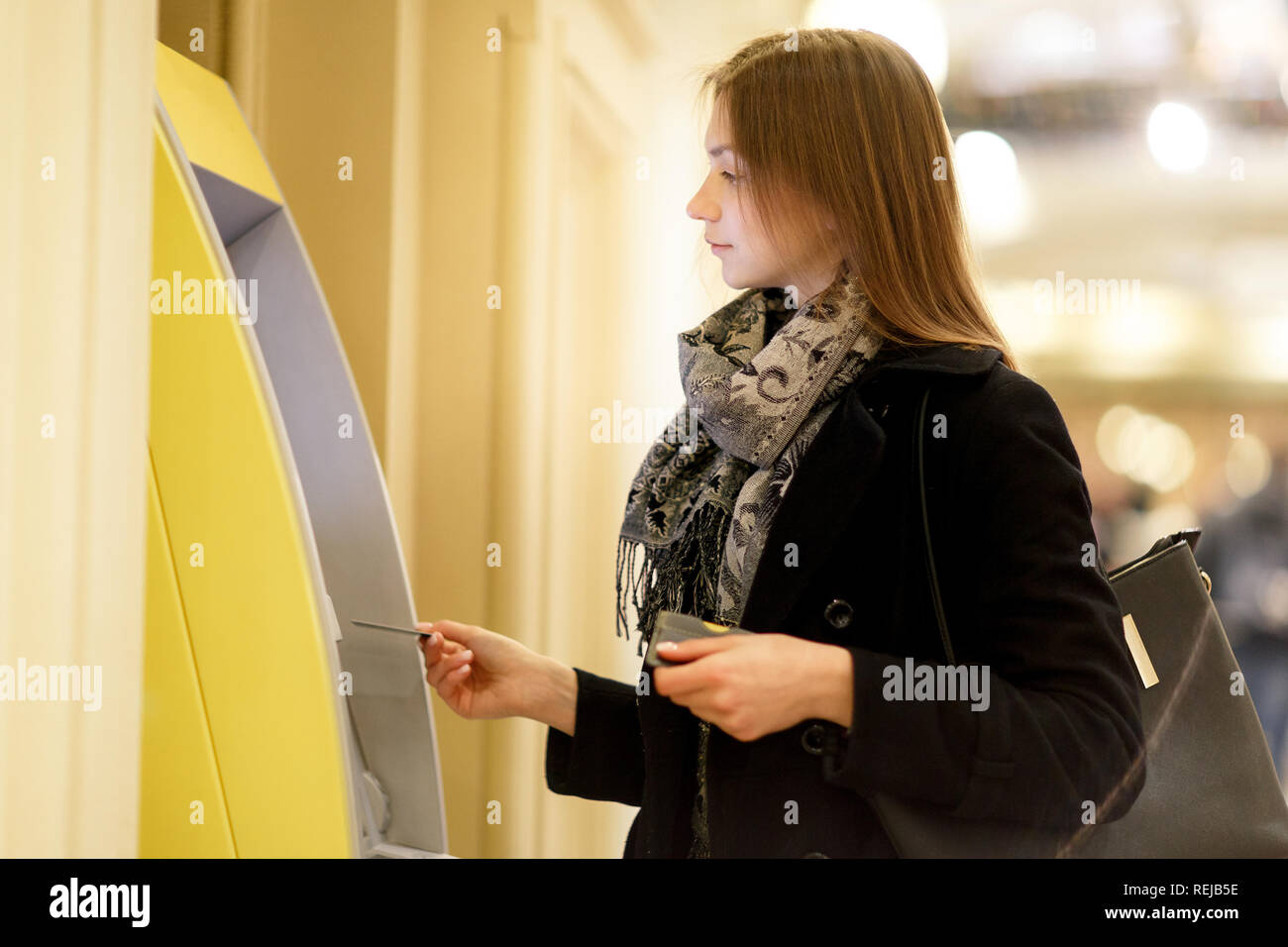 Photo of young brunette with bank card at ATM on blurred background - Stock Image