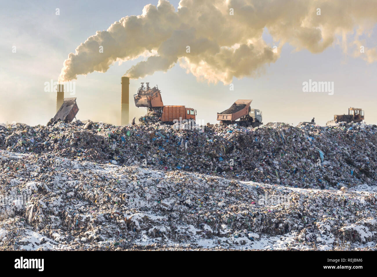 Dump trucks unloading garbage over vast landfill. Smoking industrial stacks on background. Environmental pollution. Outdated method of waste disposal. Survival of times past - Stock Image
