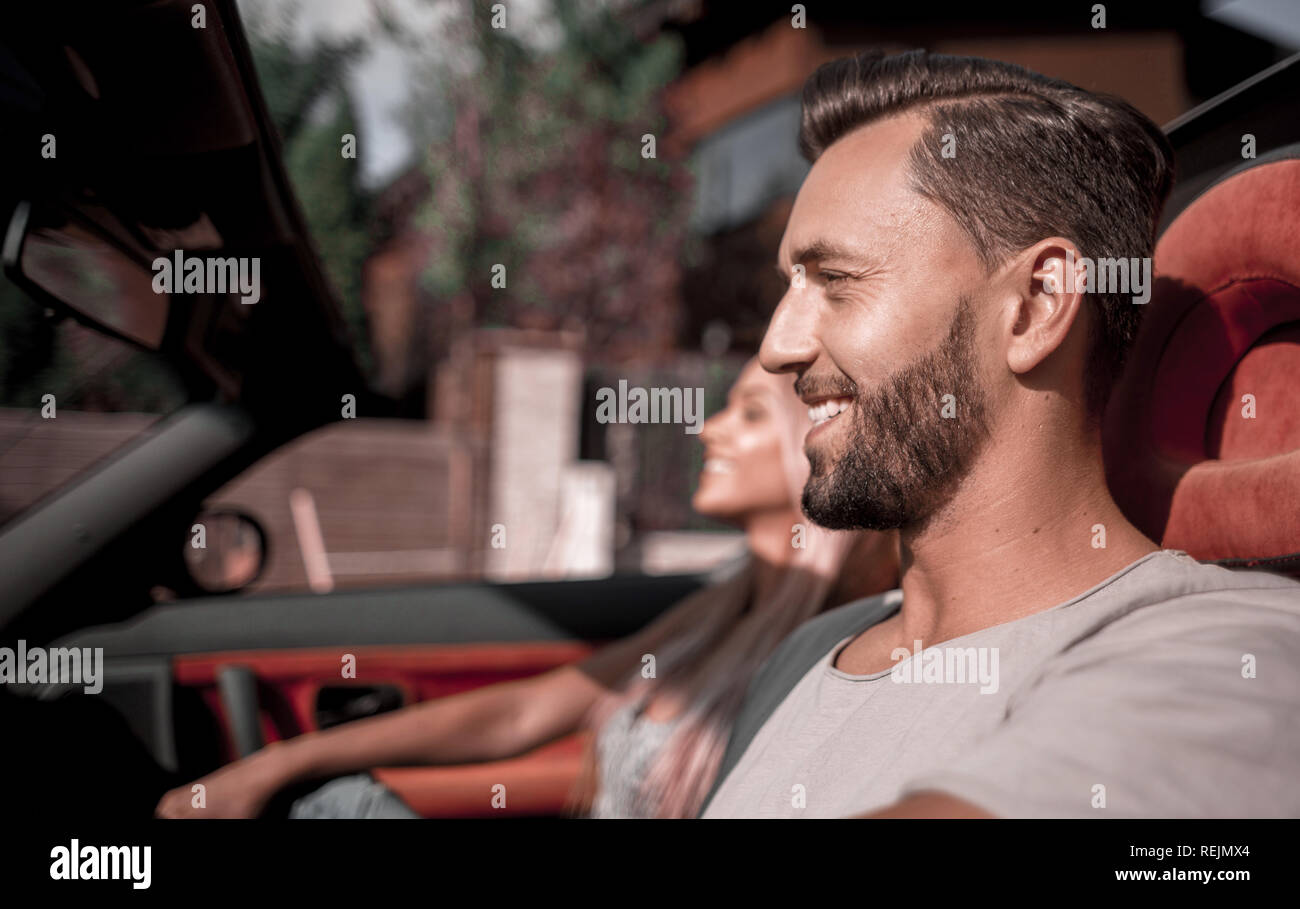 close up.handsome man driving a convertible car. - Stock Image