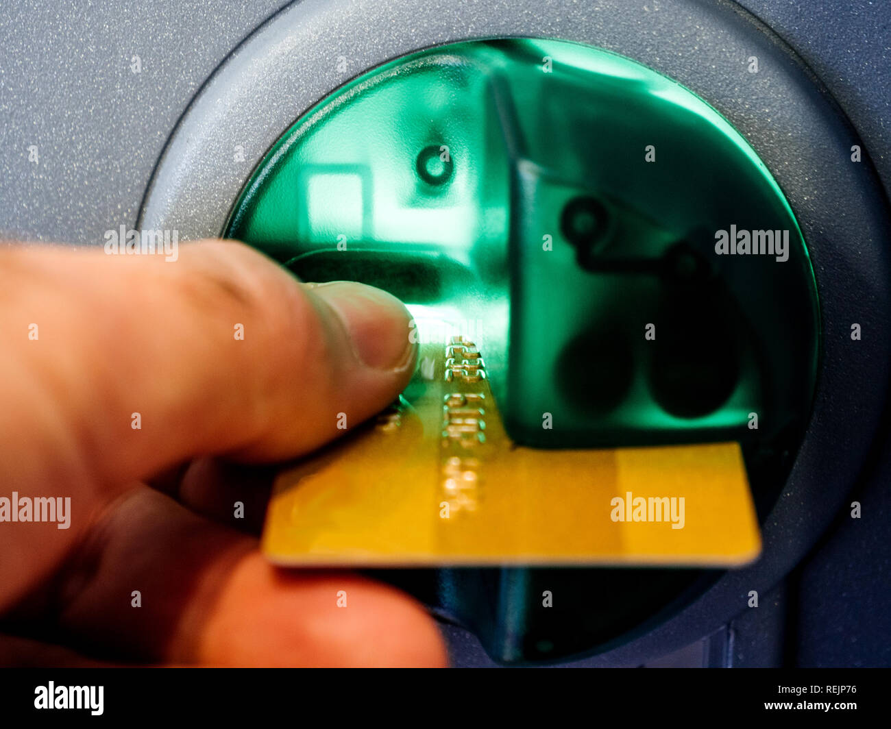 Close-up of an adult man's hand inserting a debit card into the slot of an automatic teller machine (ATM) enabling him to perform financial transactions without the need for direct interaction with the bank staff. - Stock Image