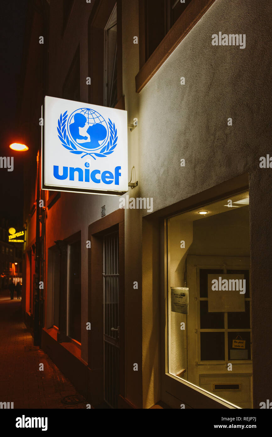 TRIER, GERMANY - FEB 21, 2015: German street at night with UNICEF illuminated insignia above the entrance door of the local branch of the international organization in Trier, Germany - Stock Image