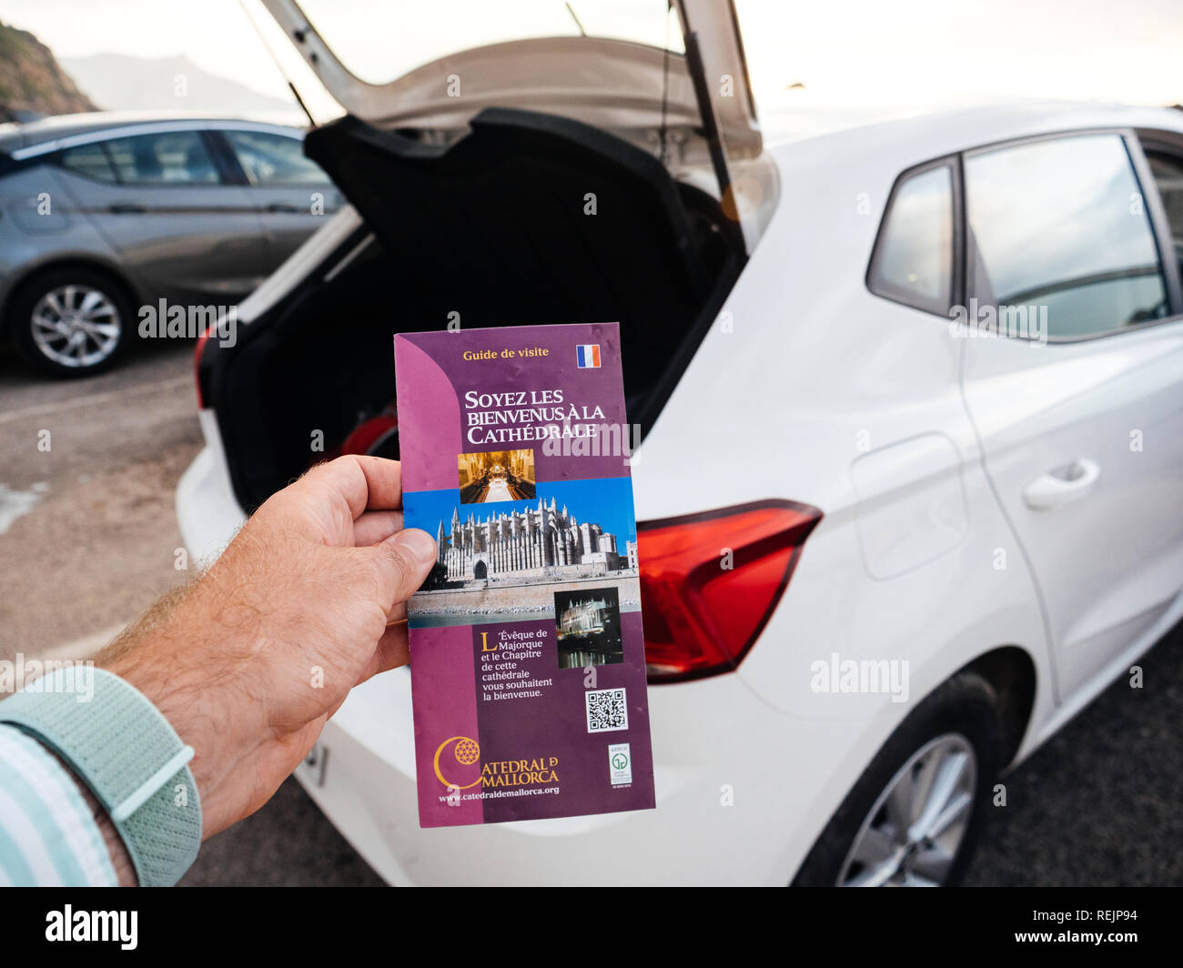 Port de Valldemosa, Palma de Malloca, Spain - May 10, 2018: Man holding point of view the touristic guide of the Santa Maria of Palma Cathedral in the parking near the open car trunk - Stock Image