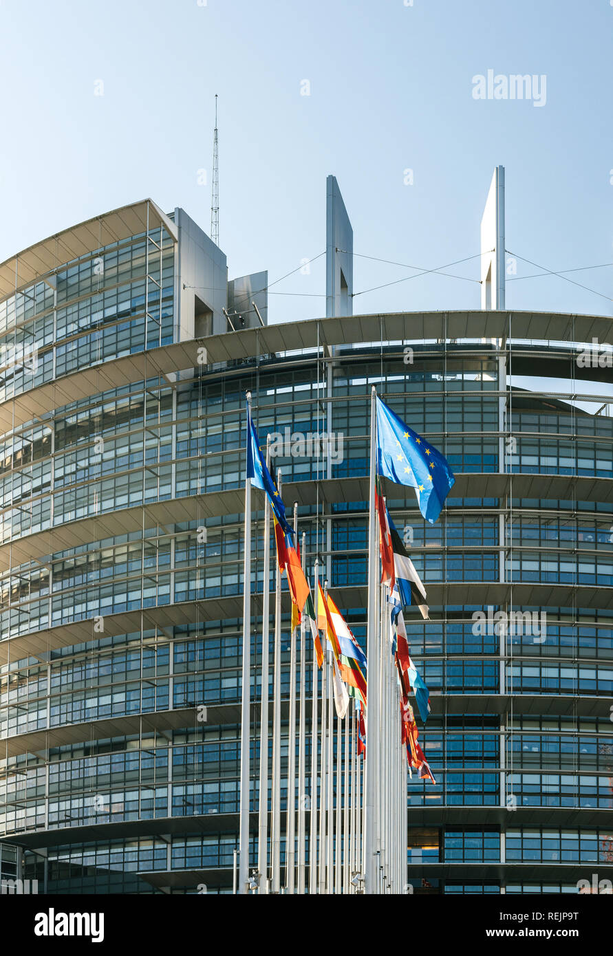 Facade of the European Parliament building in Strasbourg, France with all European Union Member States flags waving in the courtyard of the Louise Weiss building on a fine sunny spring day - Stock Image