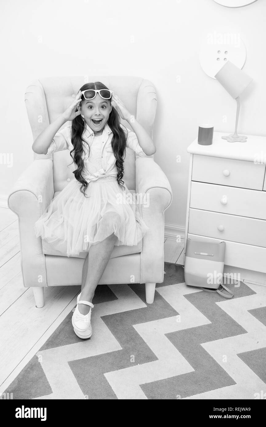 Comfortable place to rest. Girl sit chair fashionable outfit. Child girl happy face relax on shopping. Fashionista excited about shopping. Kids boutique fashion clothes salon. She is fashion addicted. - Stock Image