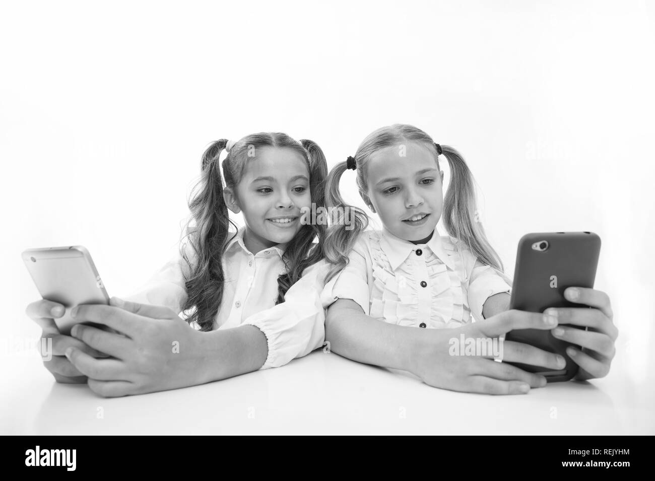 blogging at school and internet dependence. little happy girls blogging on smartphones. little girls back to school. technologies making life easier. internet dependence - Stock Image
