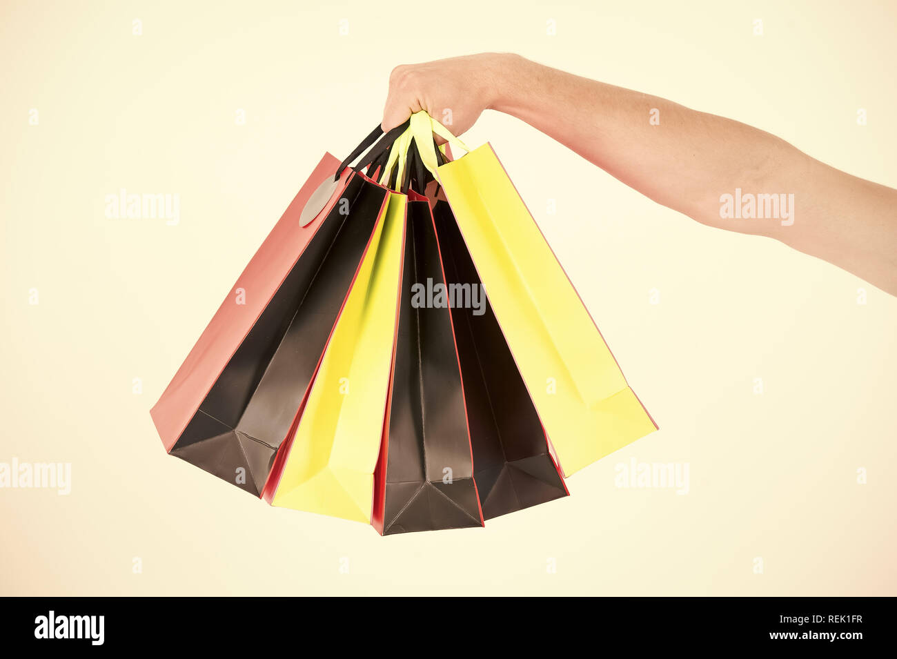 Male hand holds five shopping bags. Shopping concept. Hand holds bunch of colorful shopping bags. Shopping on black friday. Client bought lot items with discount. - Stock Image