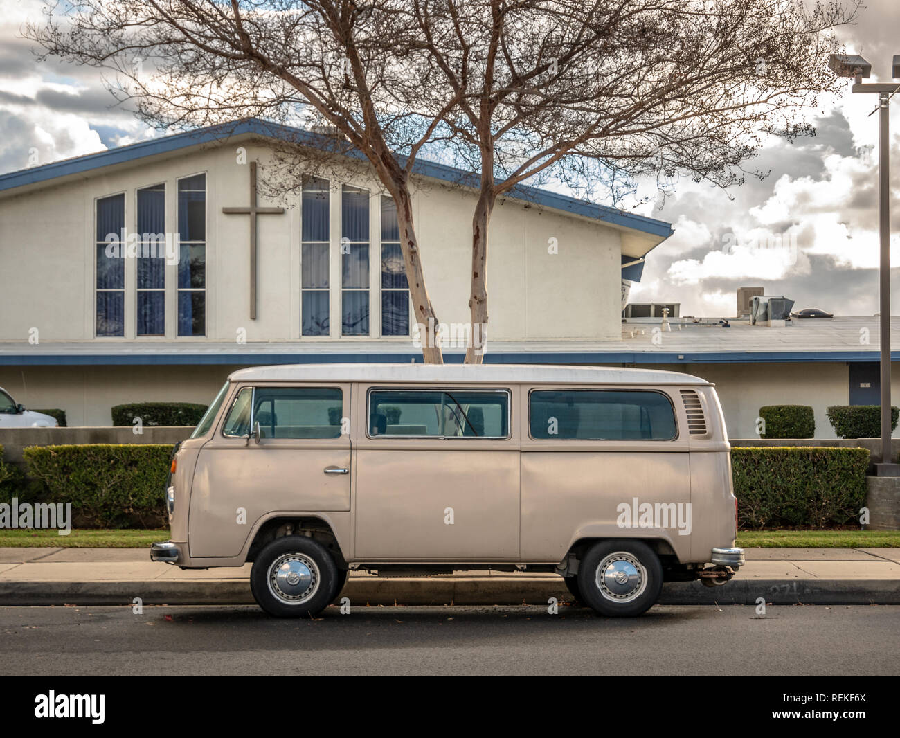 A vintage VW bus parked on the street in front of church. - Stock Image