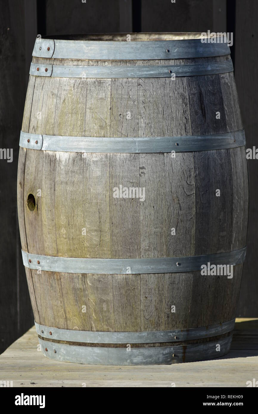 Vintage slate wooden barrel with bit weathered staves surface and galvanized hoops and cylindrical hole in middle where diameter is largest. - Stock Image
