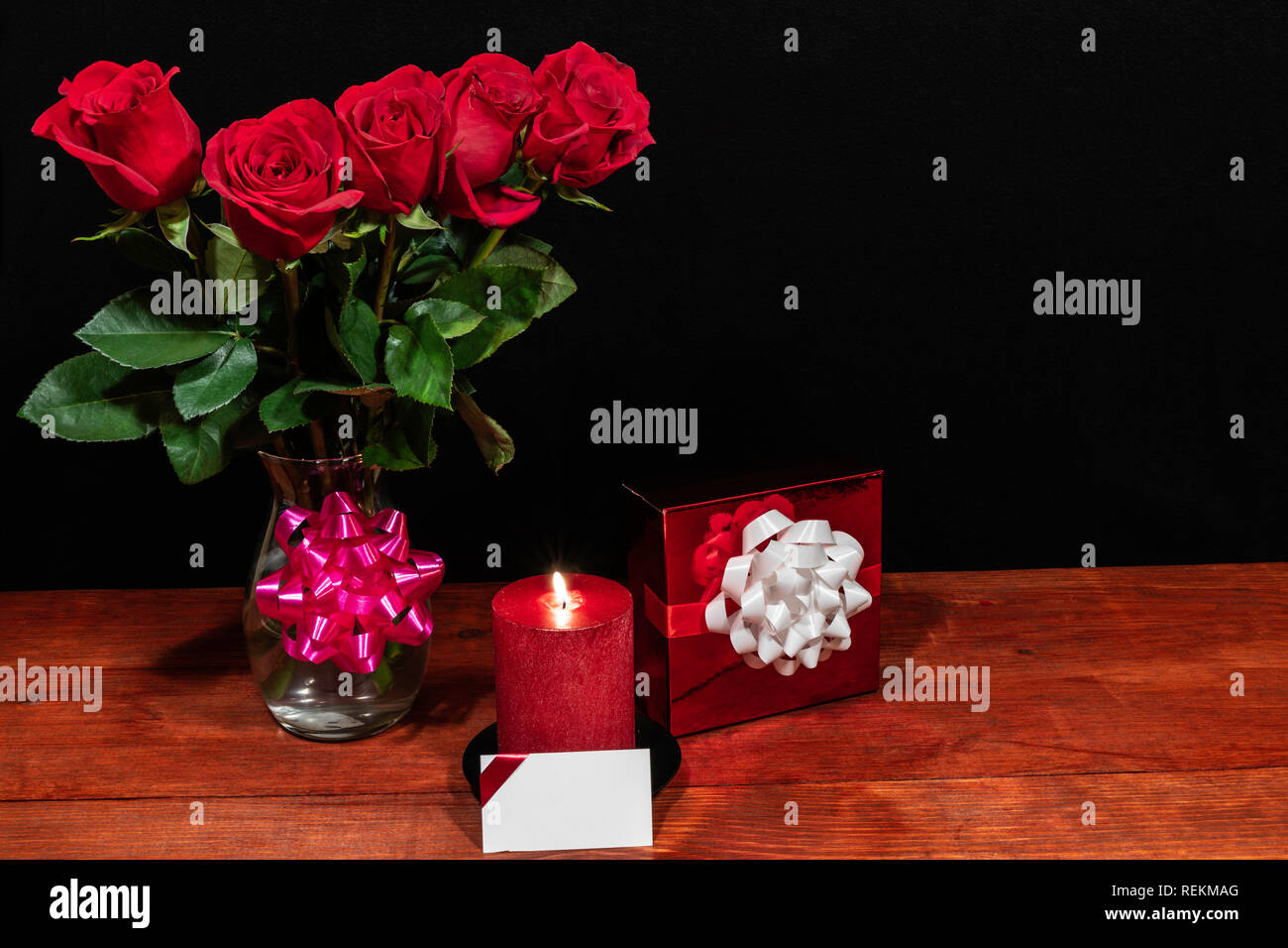 Beautiful red roses in vase with pink bow wrapped present and red candle with name tag on wooden table on dark background. Valentines, Mothers Day, Ea Stock Photo