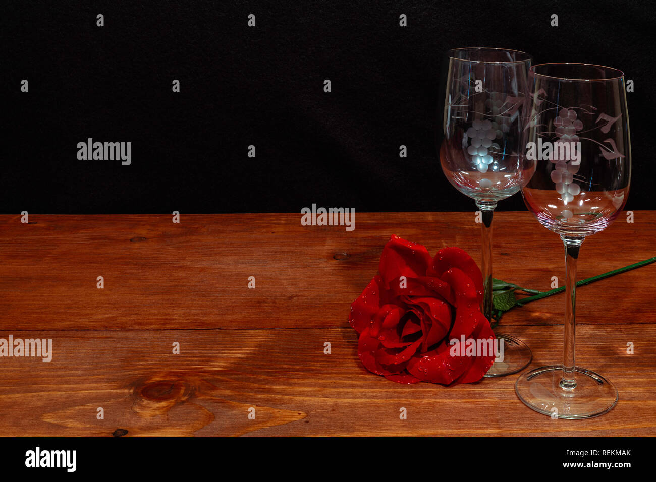 Beautiful etched wine glasses with a single red rose on wooden table and dark background. Valentines, Mothers Day, Easter, Christmas, Wedding Concepts Stock Photo