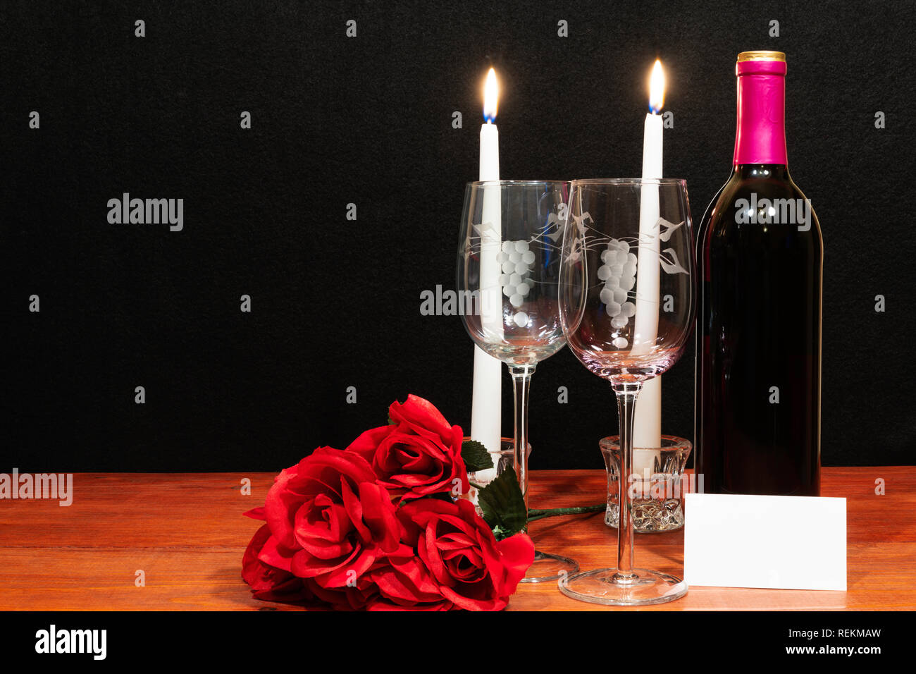 Beautiful etched wine glasses and bottle of red wine, white candles and red roses on wooden table with name tag on dark background. Valentines, Mother Stock Photo