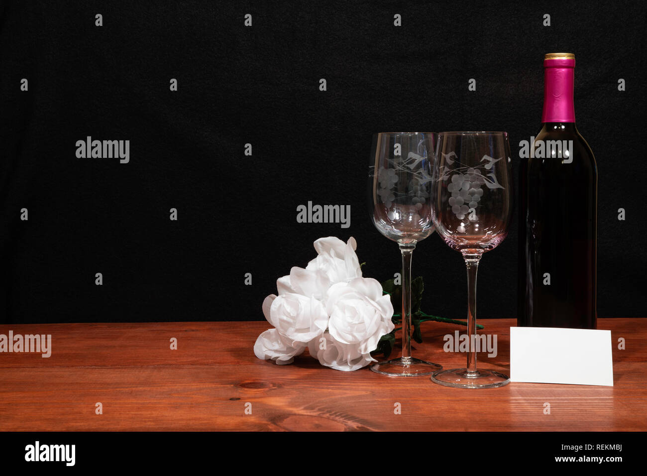Beautiful etched wine glasses and bottle of red wine and white roses on wooden table with name tag on dark background. Valentines, Mothers Day, Easter Stock Photo