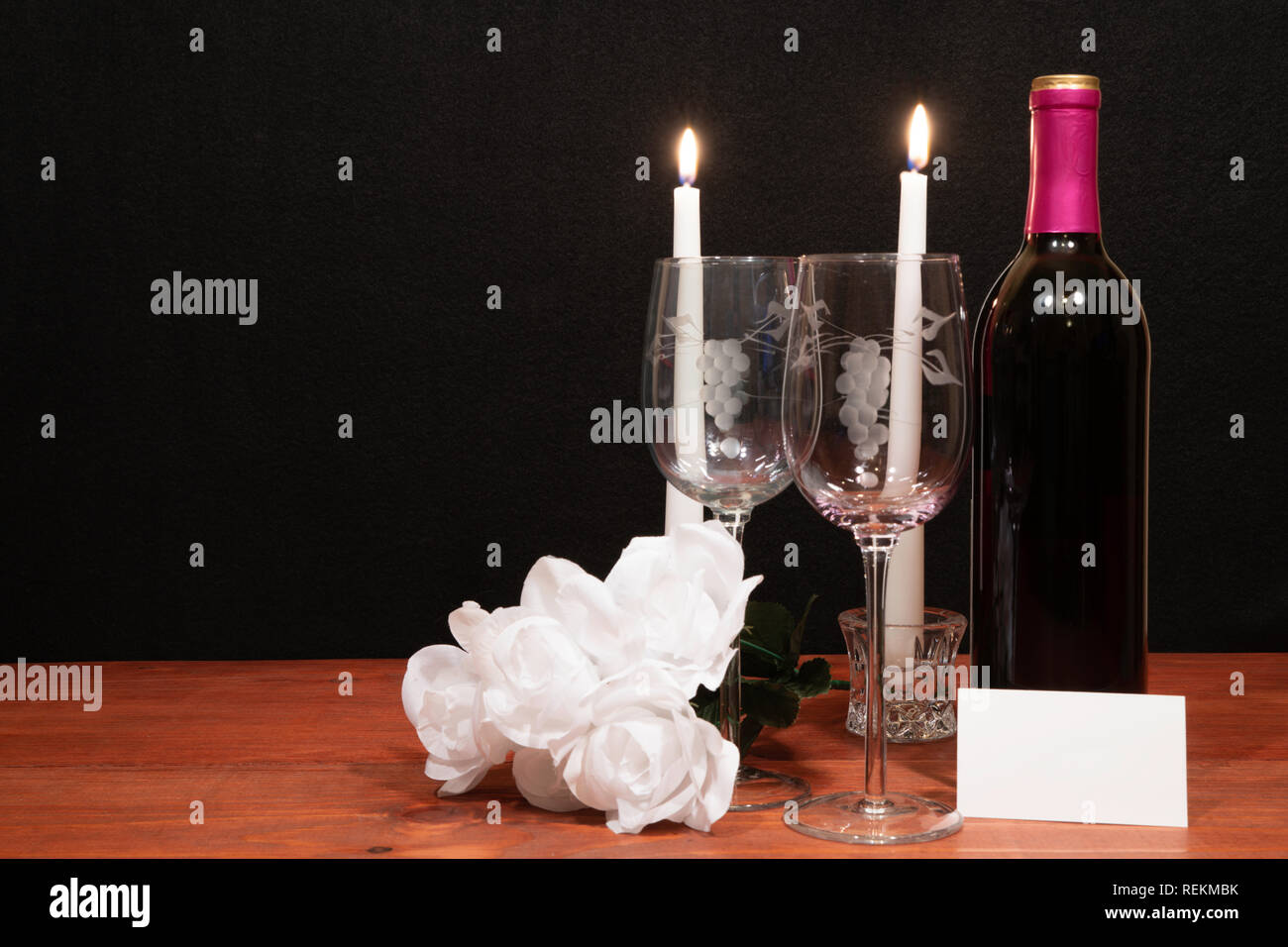 Beautiful etched wine glasses and bottle of red wine, white candles and white roses on wooden table with name tag on dark background. Valentines, Moth Stock Photo