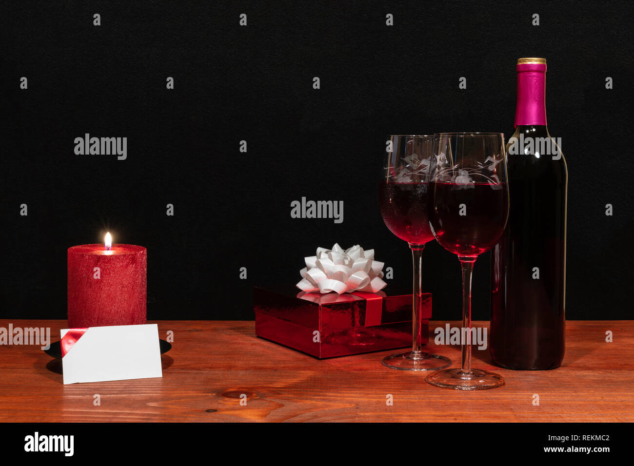 Beautiful etched wine glasses and bottle of red wine, red candle, wrapped present with bow on wooden table with name tag on dark background. Valentine Stock Photo