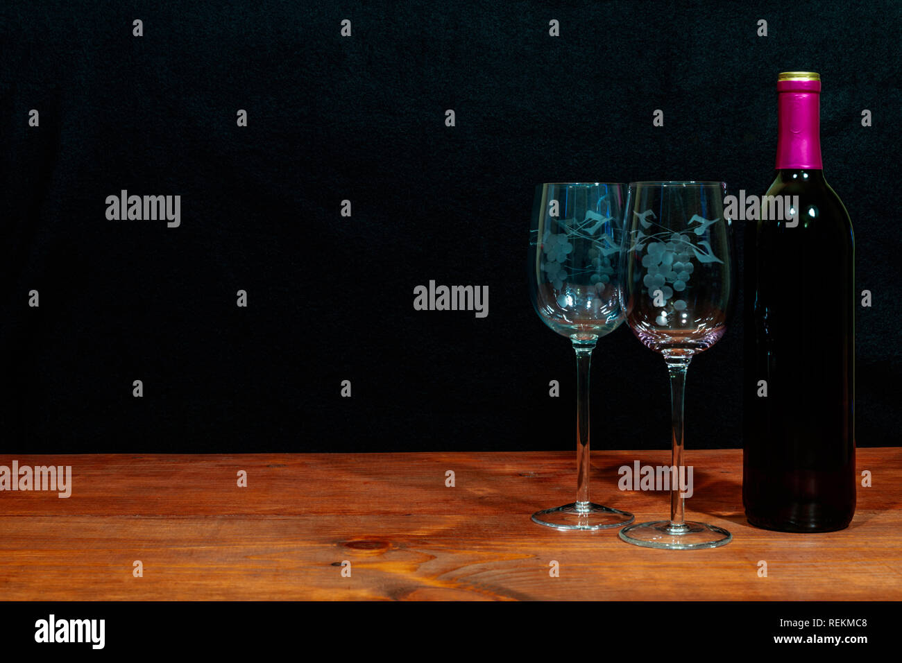 Beautiful etched wine glasses and bottle of red wine on wooden table and dark background. Valentines, Mothers Day, Easter, Christmas, Wedding Concepts Stock Photo