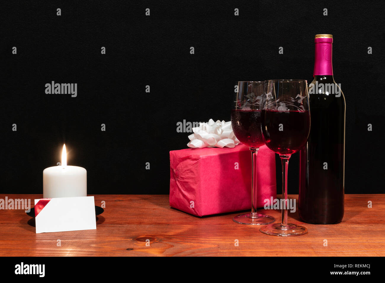 Beautiful etched wine glasses and bottle of red wine, white candle, wrapped present with bow on wooden table with name tag on dark background. Stock Photo