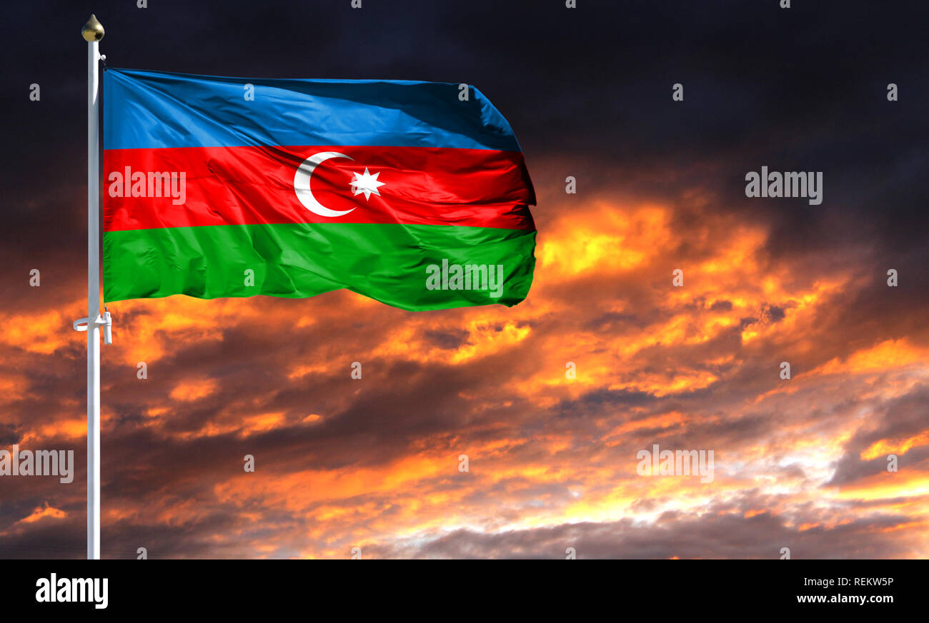 flag of Azerbaijan on flagpole fluttering in the wind against a colorful sunset sky. - Stock Image