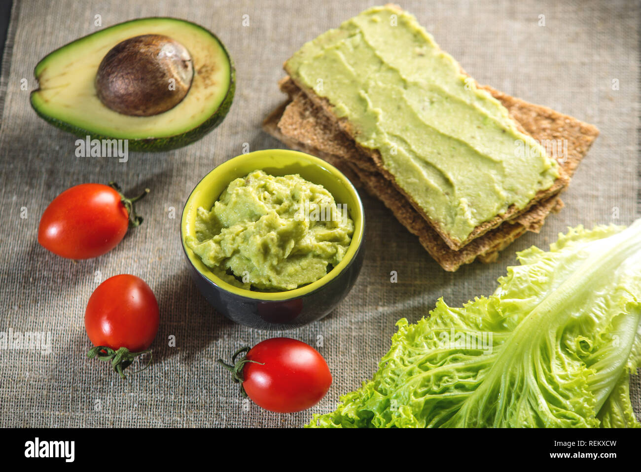 Traditional Mexican cold appetizer made of pureed avocado pulp with bread and vegetables on the table. Concept healthy vegetarian Breakfast - Stock Image
