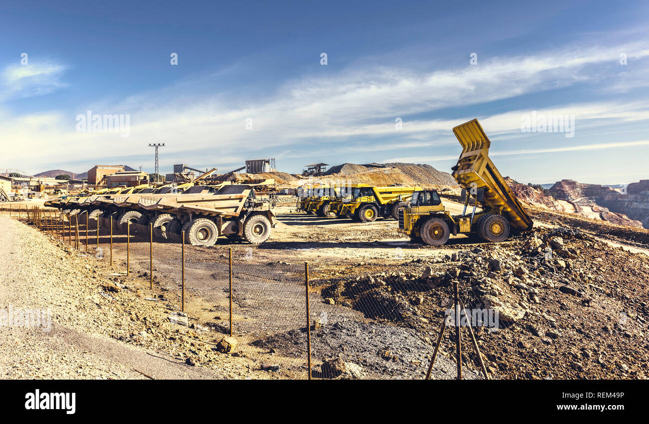 Dumper truck tilting the ore load in the open pit mine of Riotinto, with other dumper trucks parking lot and old building mining, with the cloudy sky  - Stock Image