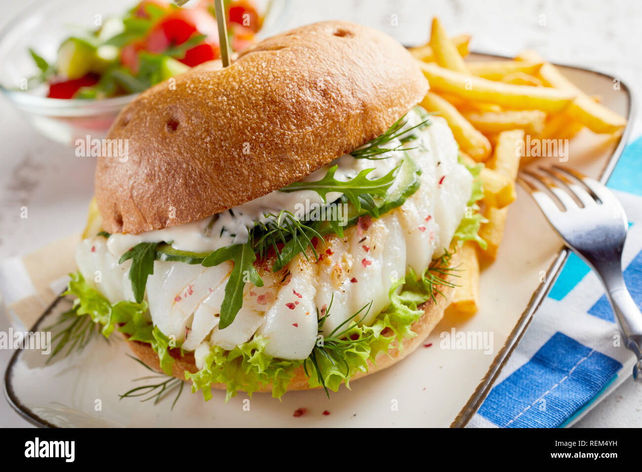 Gourmet fish seafood burger with mayo and fresh salad greens and herbs on a crusty bun with side serving of potato chips - Stock Image