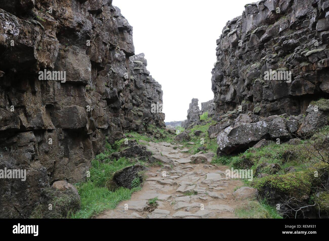 steiniger Weg durch zwei Steinwände hindurch in Thingvellir in Island an dem zwei Erdplatten angrenzen, Iceland Stock Photo
