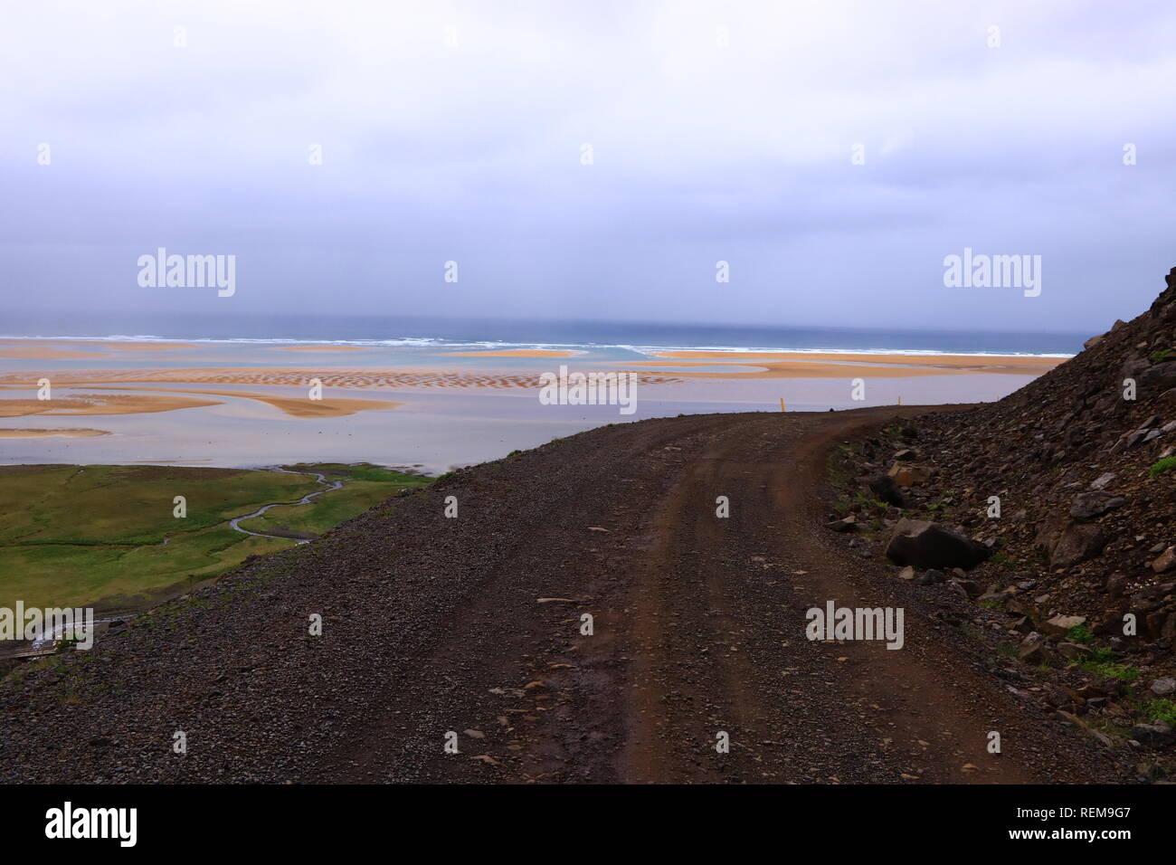 Steinige Straße zum Meer, Island - Stock Image