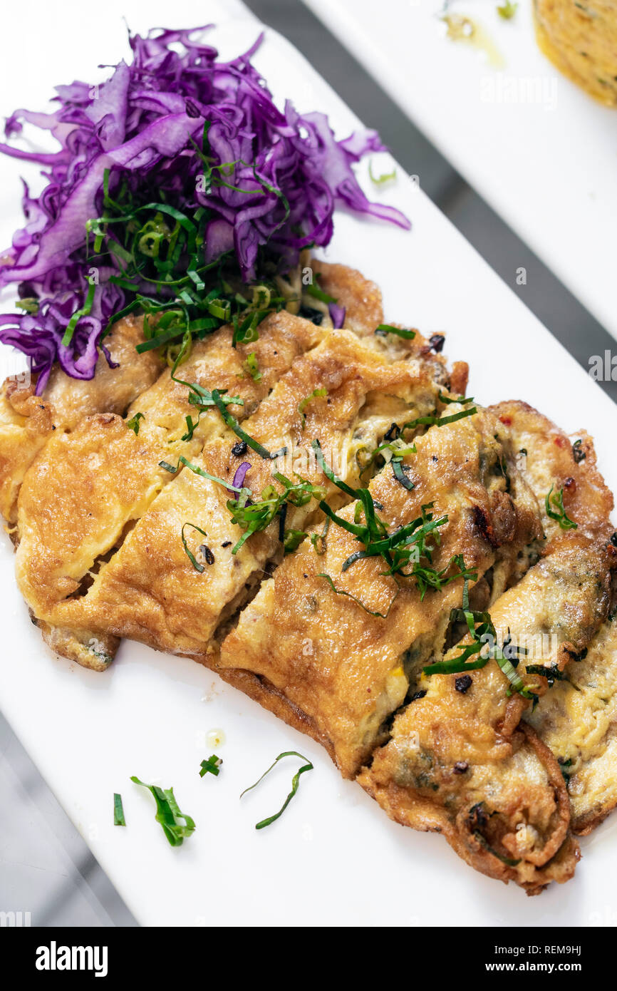 spicy chorizo and mushroom omelette with red cabbage salad tapas snack in lisbon restaurant - Stock Image
