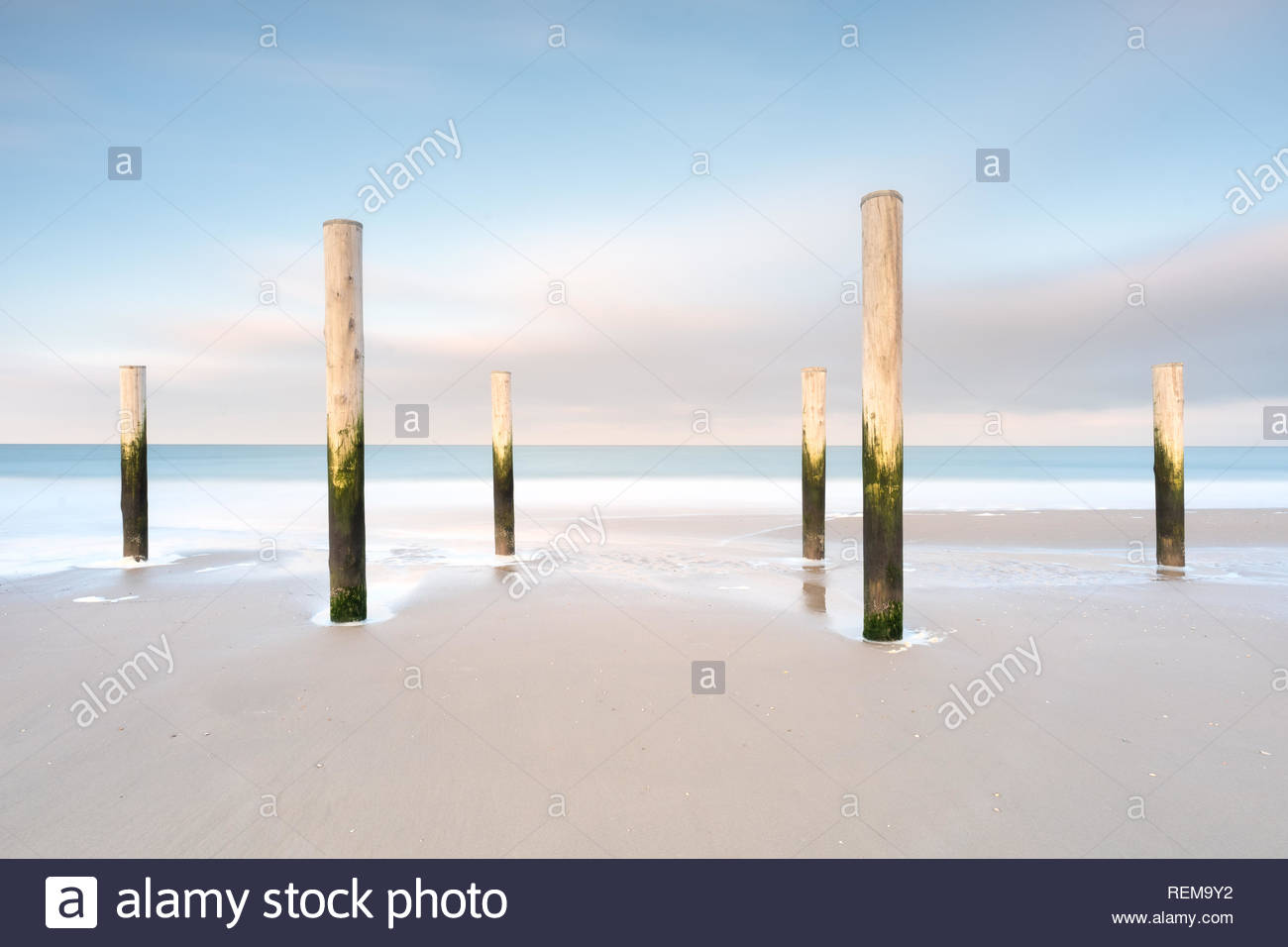 Poles on a beach with blue sky long exposure landscape Stock Photo