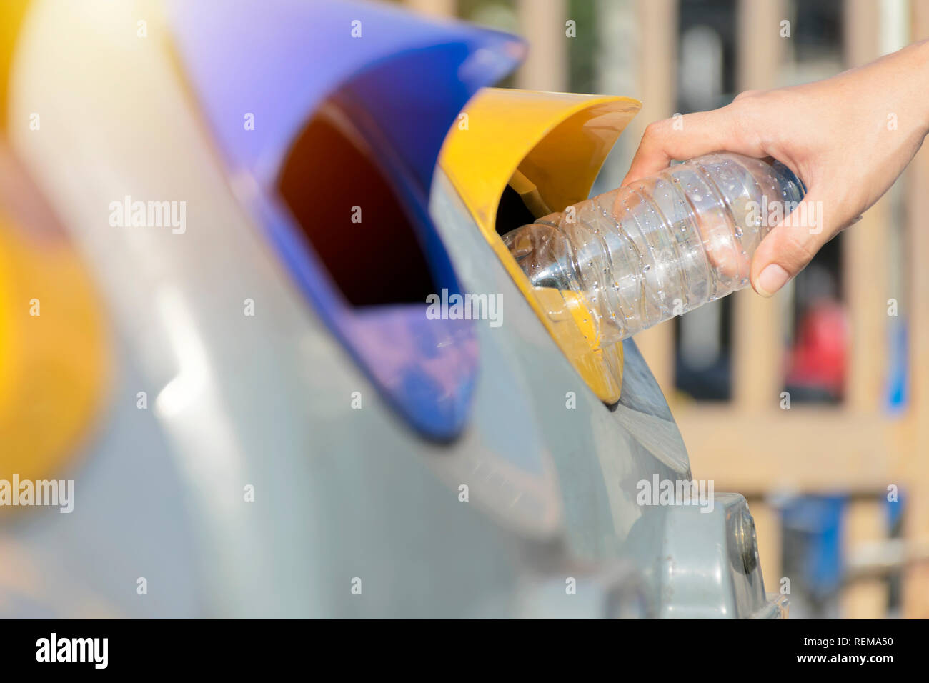 Close up hand throwing empty plastic bottle into the trash Recycling Concept. Dispose of recyclable waste to be able to reuse. - Stock Image