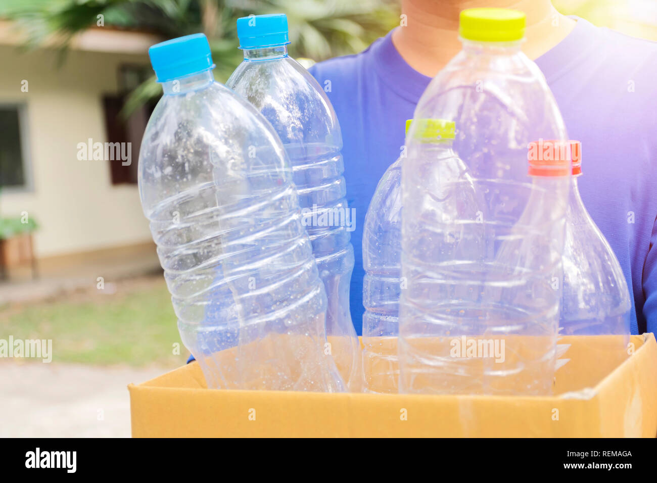 Man holds a paper box with a plastic bottle. To bottle the product. Recycling plastic bottles. It is a campaign concept for the environment. - Stock Image
