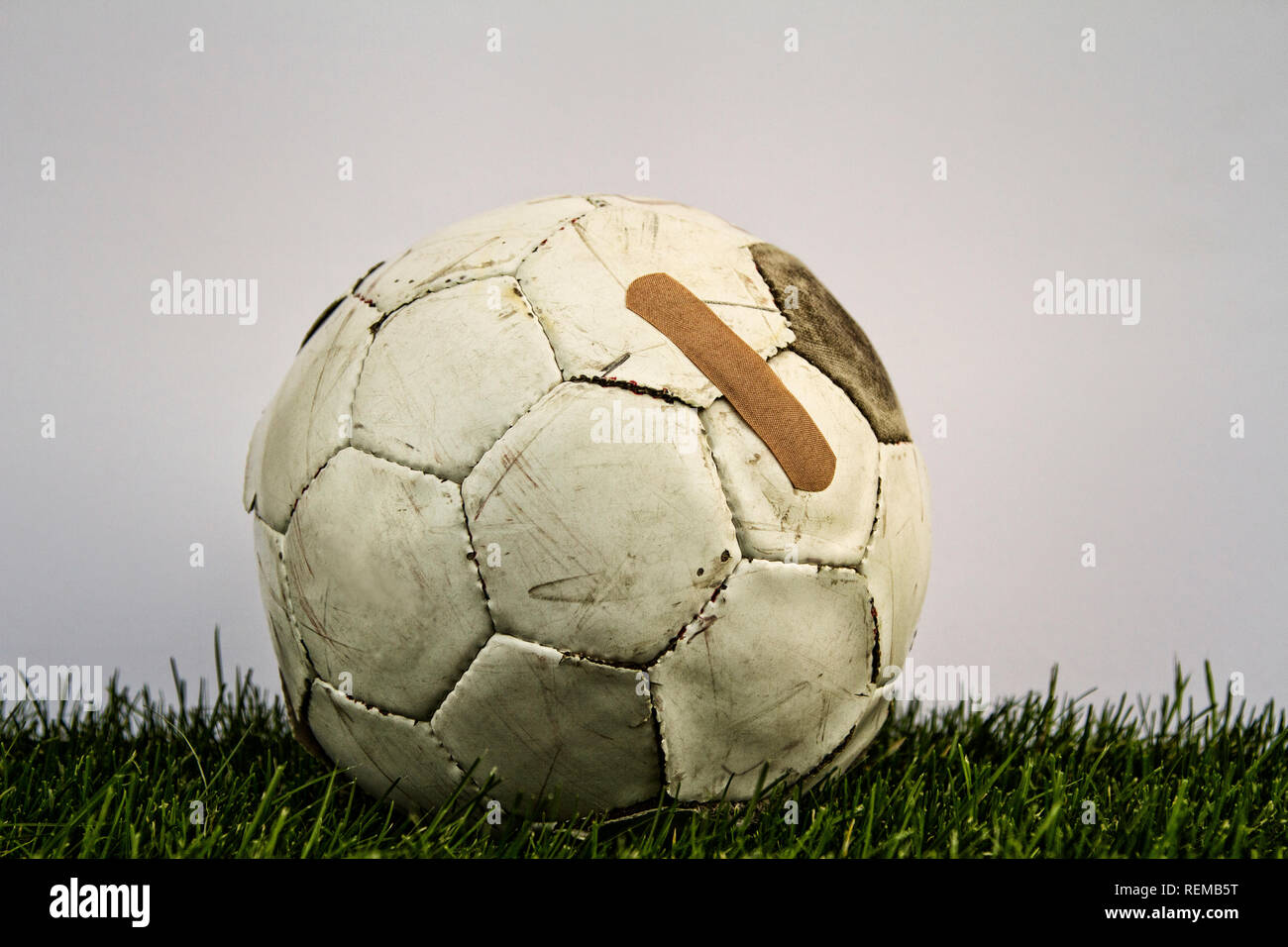 Old soccer ball with band aid on grass with white background - Stock Image
