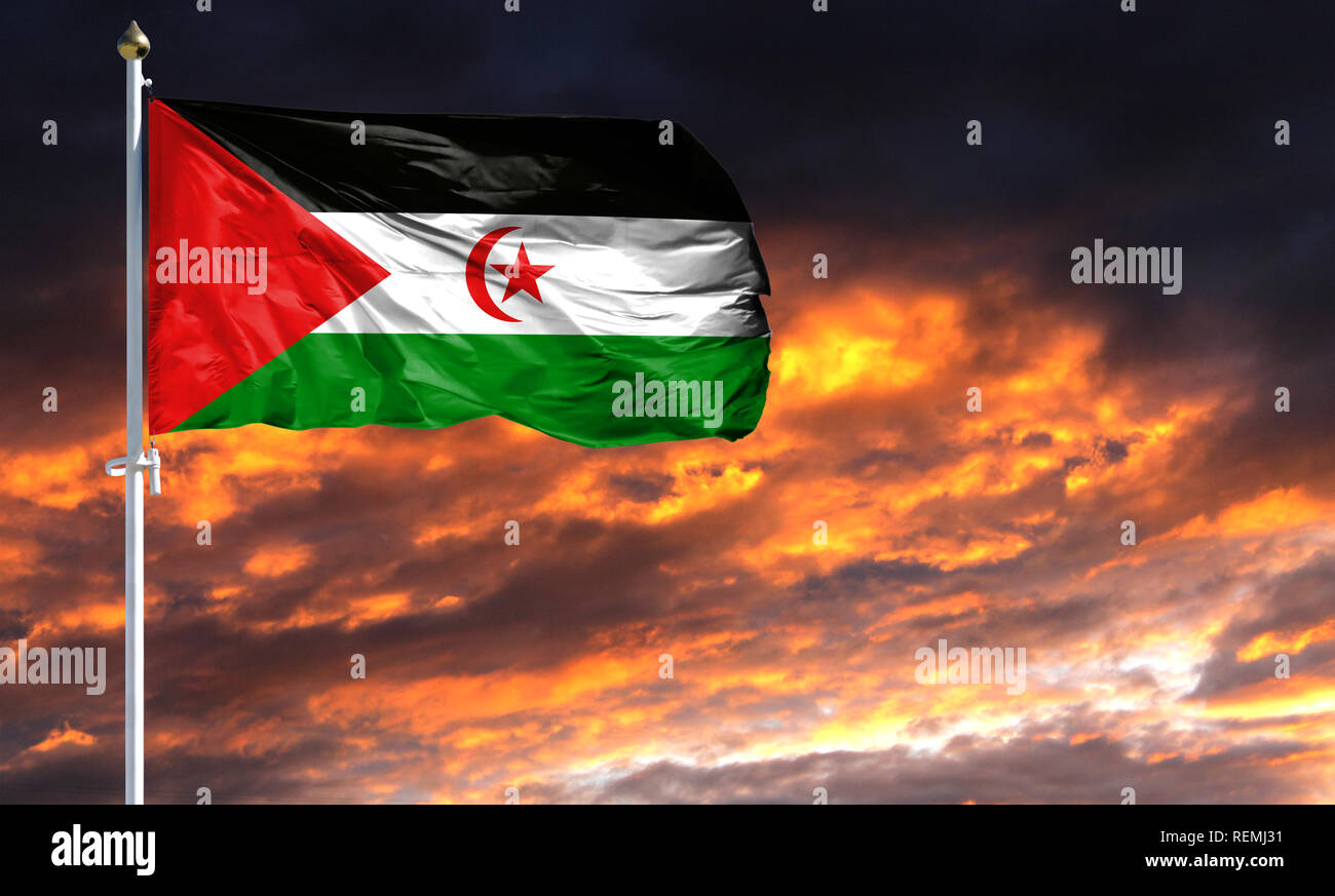 flag of Western Sahara on flagpole fluttering in the wind against a colorful sunset sky. - Stock Image