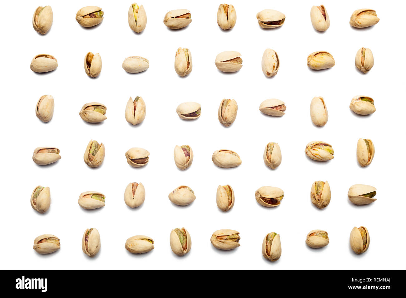 2fb387ce6b5e6 A collection of pistachio nuts lie in horizontal rows on an isolated white  background. with