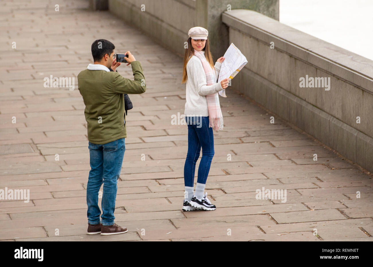 Young female tourist looking at a map being photographed by friend on the South Bank by The River Thames in London UK Stock Photo