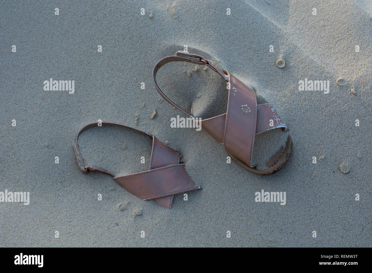 Abandoned pink sandals on a beach - Stock Image