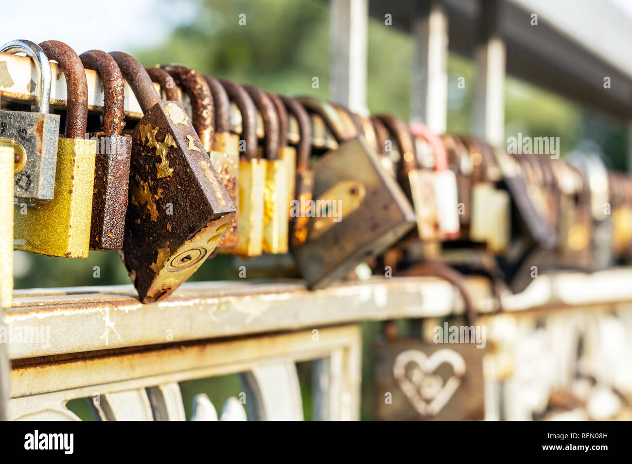 Many old rusty metal locks closed on fence of bridge over river