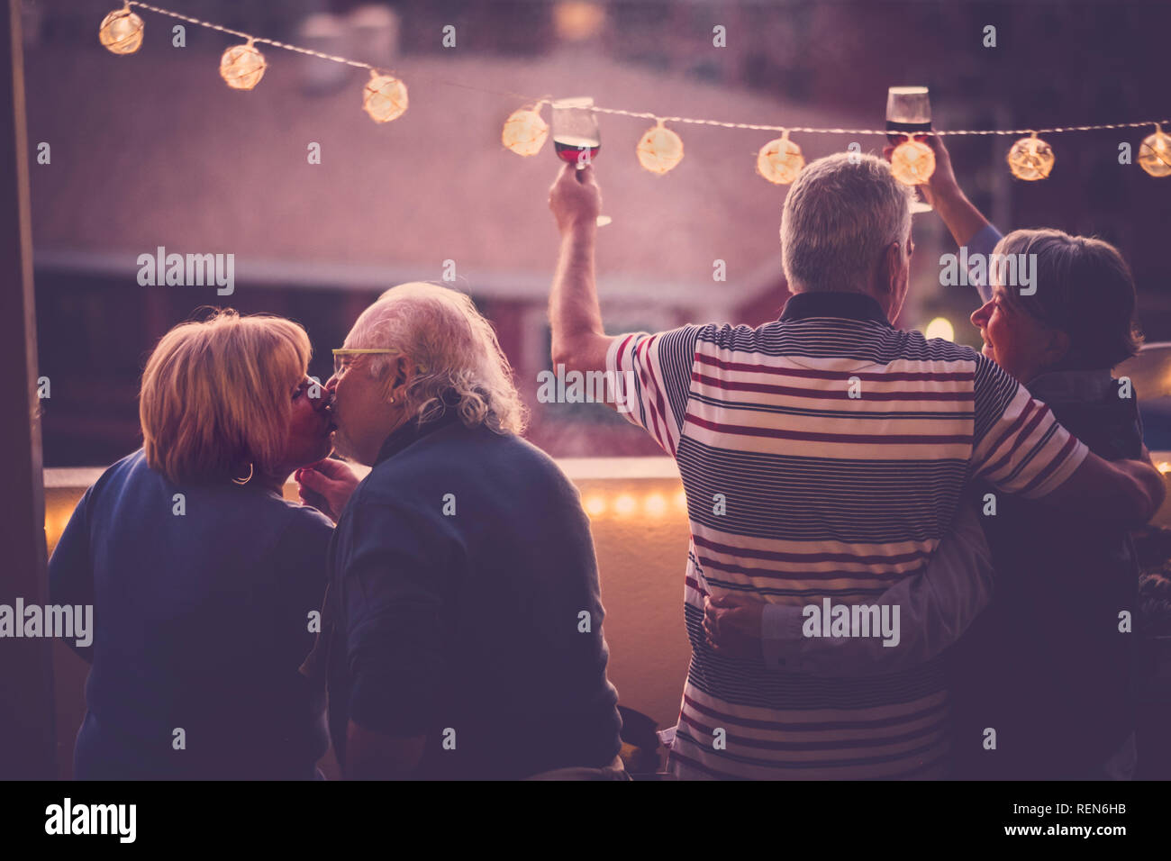 Romantic and love concept with two senior adults couple celebrate together at home in a terrace with city view - toasting with wine and kissing - matu Stock Photo