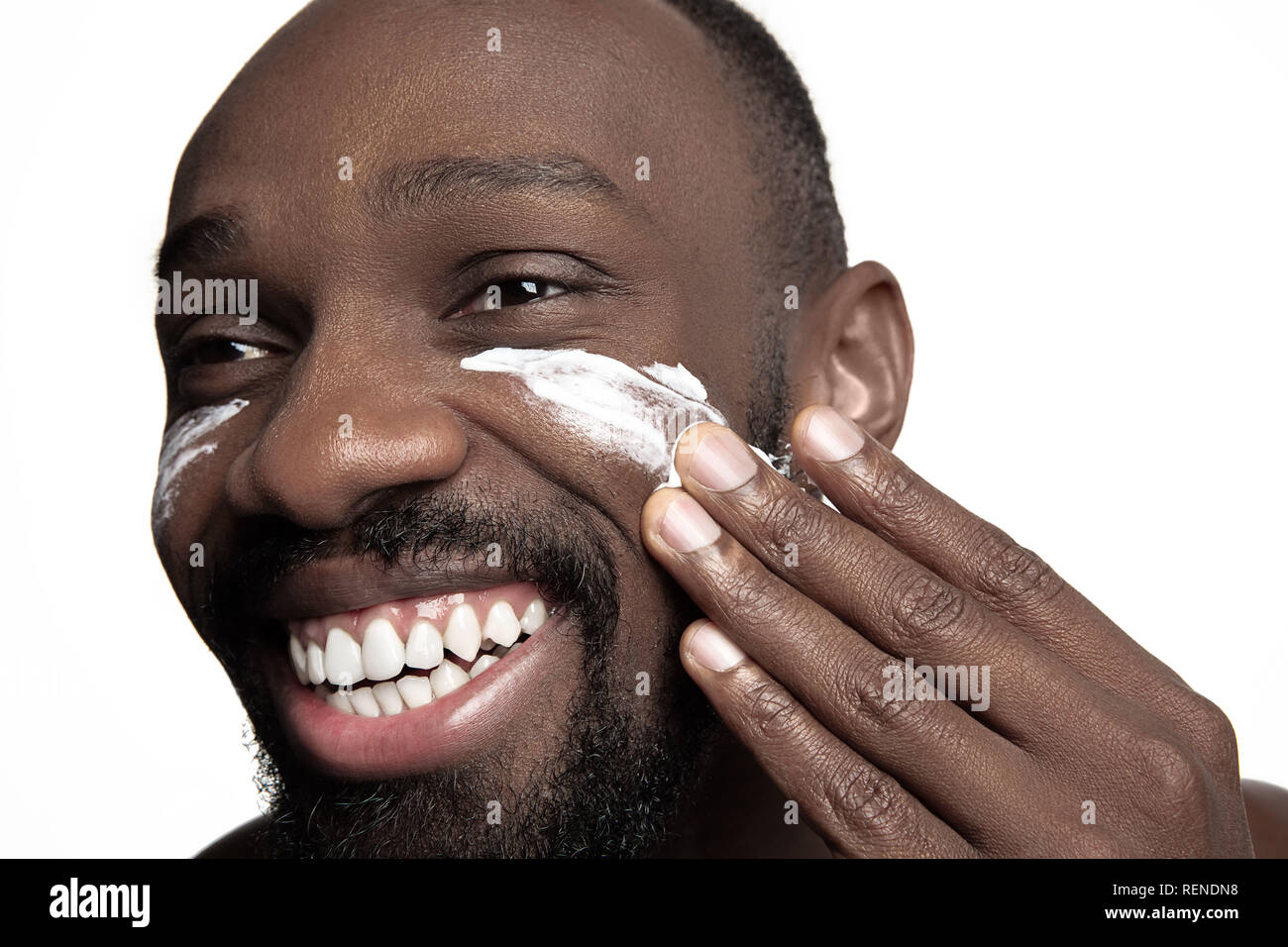 Young african-american guy applying face cream under his