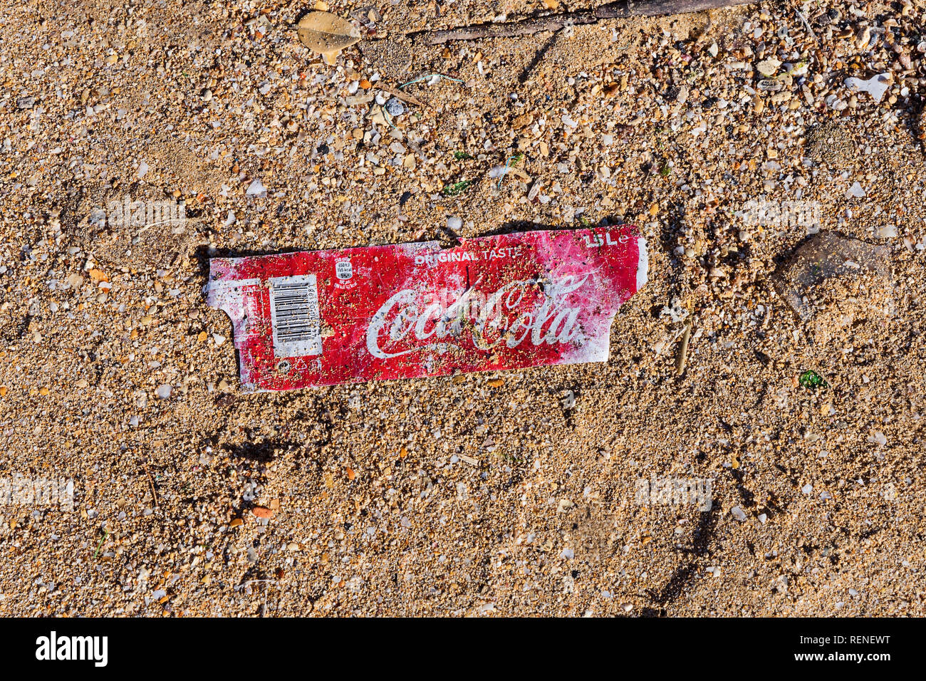 Birkirkara, Malta - December 31, 2018: Plastic label from bottle of Coca-Cola on sandy beach after storm. Plastic pollution problem environment pollut Stock Photo